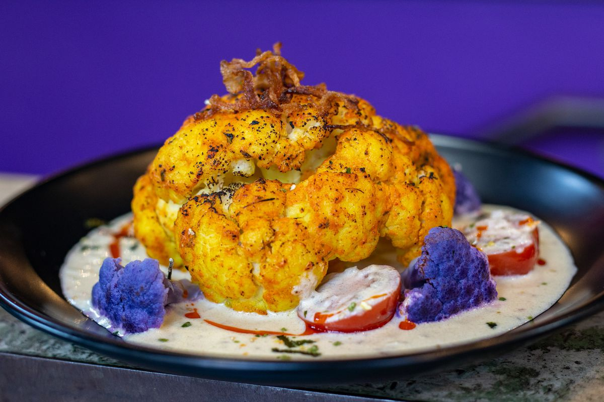 Roasted cauliflower on a bed of creamy sauce with smaller purple cauliflower and tomatoes.