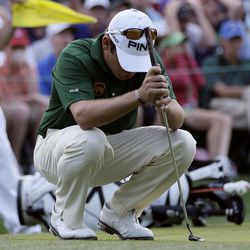 Louis Oosthuizen, of South Africa, reacts after missing a putt during a sudden death playoff on the 10th hole at the Masters golf tournament Sunday, April 8, 2012, in Augusta, Ga.