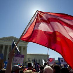 An equality flag waves during a demonstrators in front of the Supreme Court in Washington, Tuesday, April 28, 2015. The Supreme Court heard historic arguments in cases that could make same-sex marriage the law of the land.