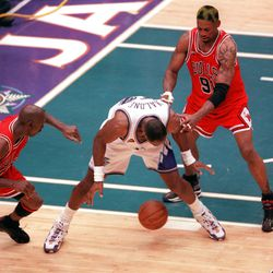 Karl Malone loses the ball for a turnover with Michael Jordan and Dennis Rodman guarding him at the end of Game 6 of the NBA Finals at the Delta Center, June 14, 1998. The turnover led to Jordan hitting the game-winning shot to give the Bulls their third-straight NBA Title.