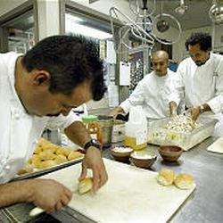 Sundance chef Jason Knibb, far right, mixes a potato salad while Jose Vazquez seasons it. In the foreground, Ruben Aguirre cuts rolls for sandwiches. Knibb leaves for the James Beard Dinner in New York Friday.