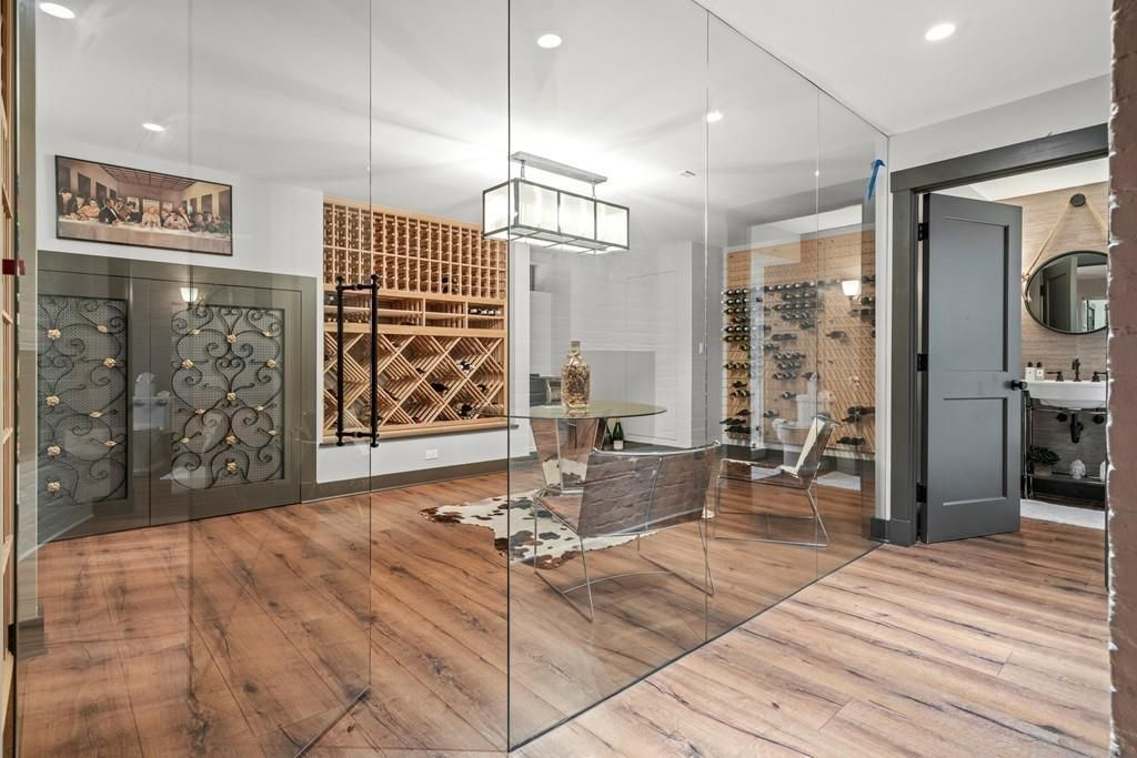 A wine-tasting room with racks for the bottles and a table and chairs, and it's all visible through a glass wall.