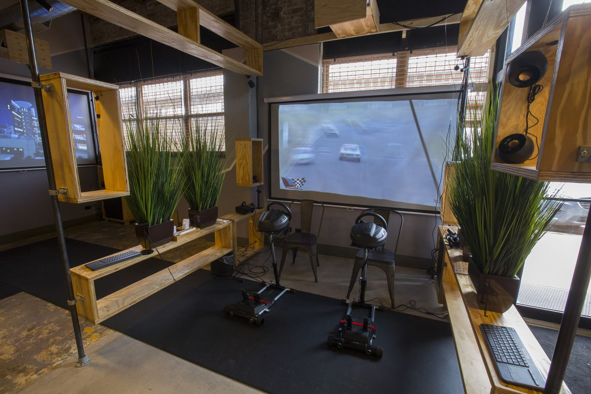 A projection screen showing a racing game with two steering wheel controllers.