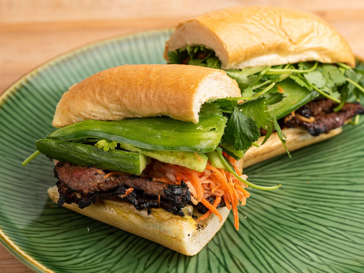 A banh mi sandwich made on a baguette and filled with lemongrass beef, pickled vegetables, cucumber, and jalapeno.