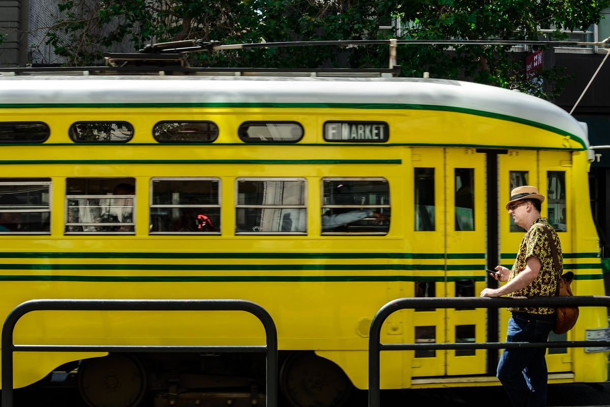 Streetcar on Market Street, yellow with green stripes.