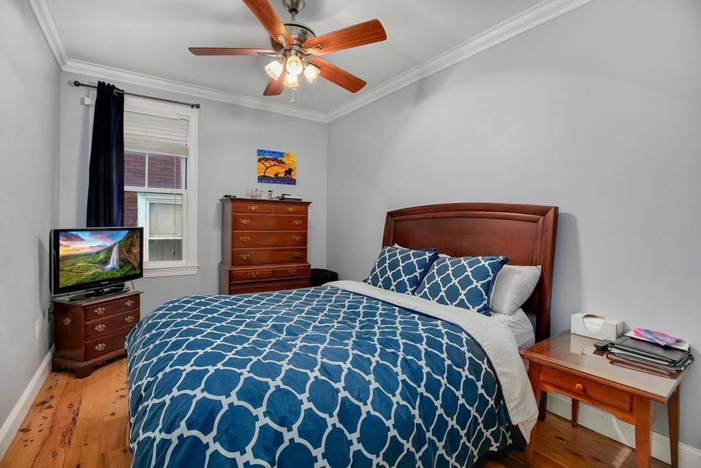 A bedroom with a bed, a TV in the corner, and a ceiling fan.