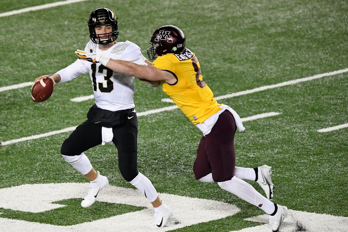 Quarterback Jack Plummer of the Purdue Boilermakers passes the ball under pressure from Thomas Rush #8 of the Minnesota Golden Gophers during the fourth quarter of the game at TCF Bank Stadium on November 20, 2020 in Minneapolis, Minnesota. The Golden Gophers defeated the Boilermakers 34-31.