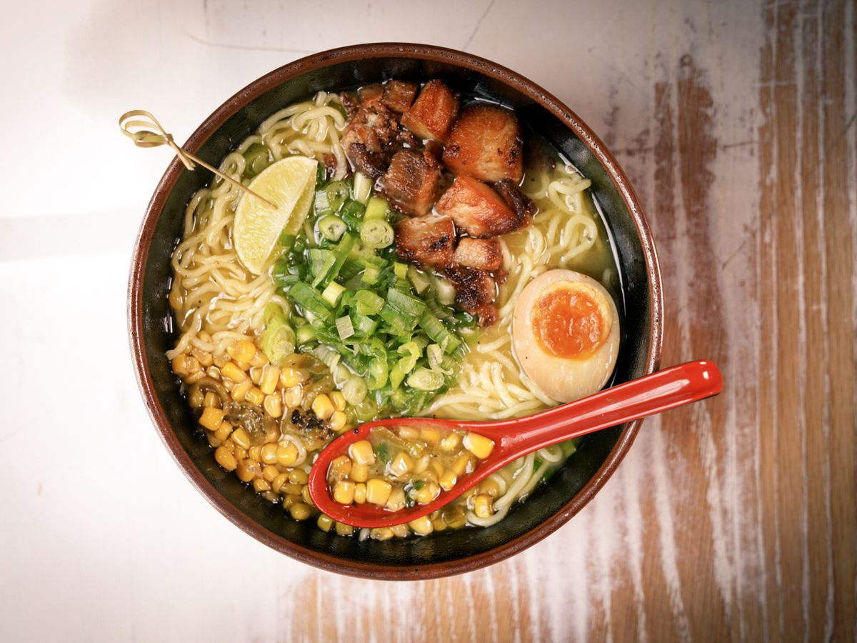 A bowl of ramen with noodles, a lime slice with a skewer, corn and corn in a soup spoon, half-egg, sliced peppers, and diced fried pork