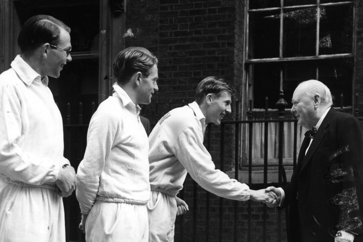 Roger Bannister shakes hands with Prime Minister Winston Churchill  as fellow runners Chris Brasher and Chris Chataway (center) look on.