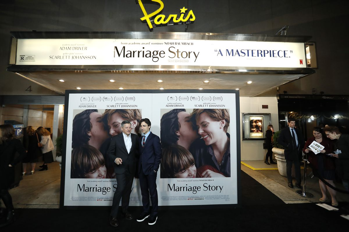 """Ted Sarandos and Noah Baumbach stand in front of a Marriage Story movie poster and the Paris Theater marquee which reads """"masterpiece"""""""