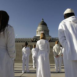 """Performers in Ernesto Pujol's durational art piece """"Awaiting"""" stand near the state Capitol in Salt Lake City Thursday. The performers, wearing all white, walked from various points in Salt Lake City to convene on the steps of the Capitol, where they walked up and down for 12 hours. Local artists and University of Utah students were involved in the performance."""