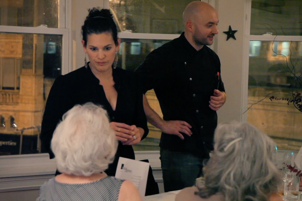 A woman and man stand in front of a dinner party.
