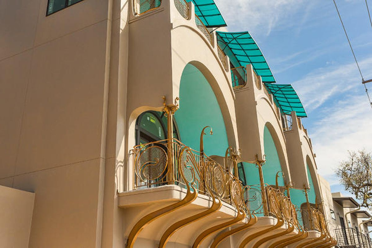 three arched balconies on second floor of stucco building, aqua ceilings, curvy gold railings