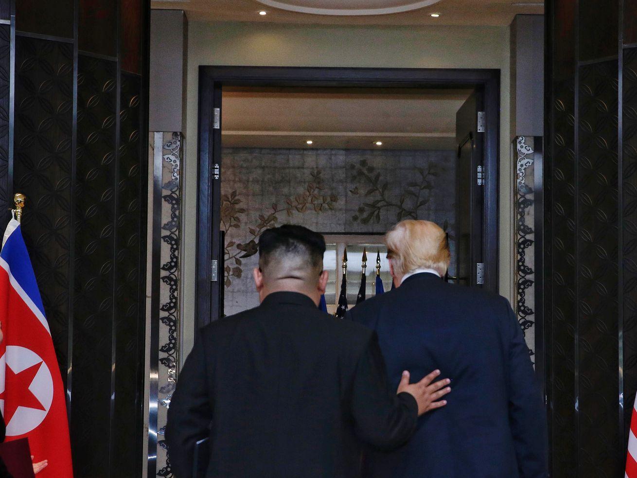 North Korean leader Kim Jong Un walks with US President Donald Trump.