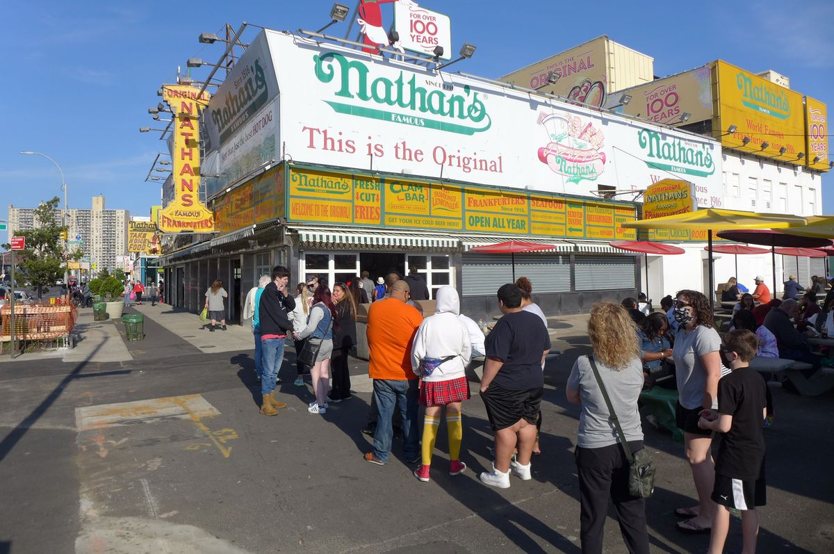 A line wends outside the Nathan's down the block with Nathan's signage visible overhead.