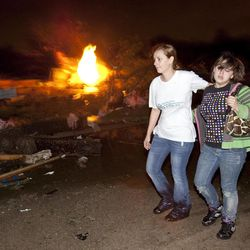 """Two people walk past a gas fire in the Pinaire mobile home park in Wichita, Kansas Saturday April 14, 2012 after a tornado caused massive destruction in the area on Saturday night. Tornadoes were spotted across the Midwest and Plains on Saturday as an outbreak of unusually strong weather seized the region, and forecasters sternly warned that """"life-threatening"""" weather could intensify overnight."""