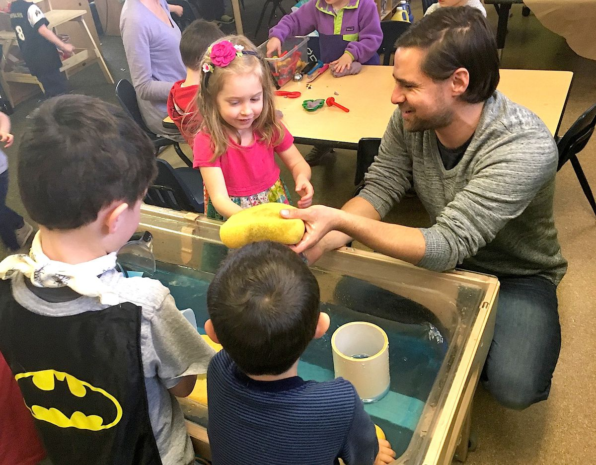 Denver preschool teacher Graham Carson plays with children at the water table.