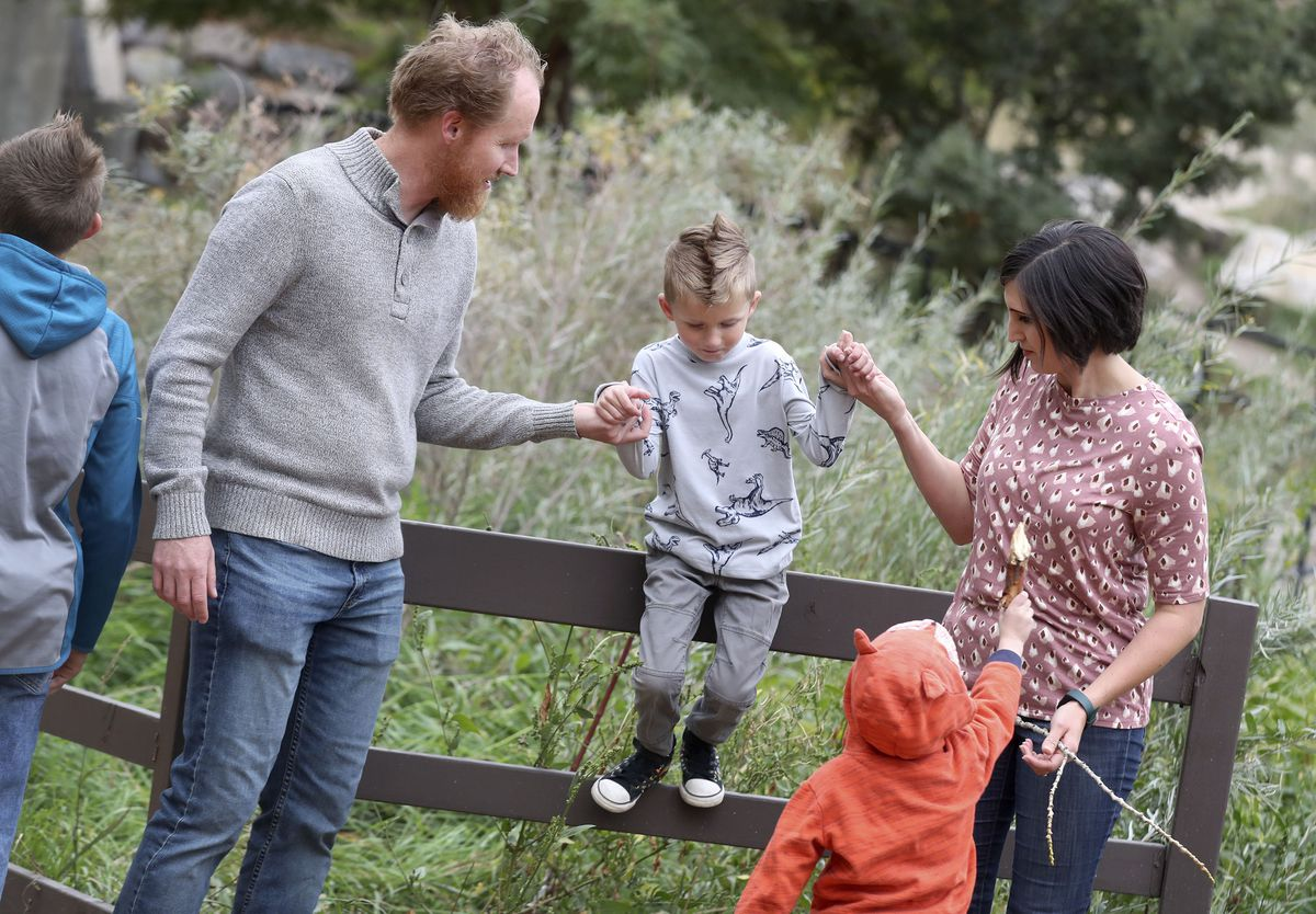 Sam and Melanie Jewkes help their son, Nico, 5, jump down from a fence during a walk near their home in Murray on Friday, Oct. 8, 2021.