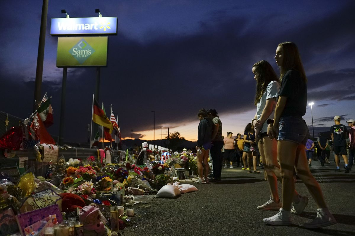 People stand at dusk at a makeshift memorial outside the Walmart in Texas where 22 people were shot and killed.