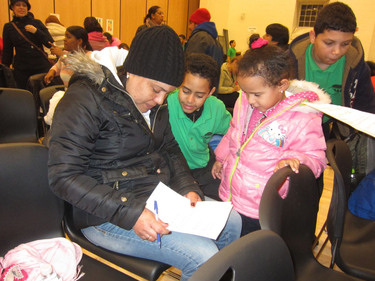 A parent gives written feedback after a presentation on the school's grading system.