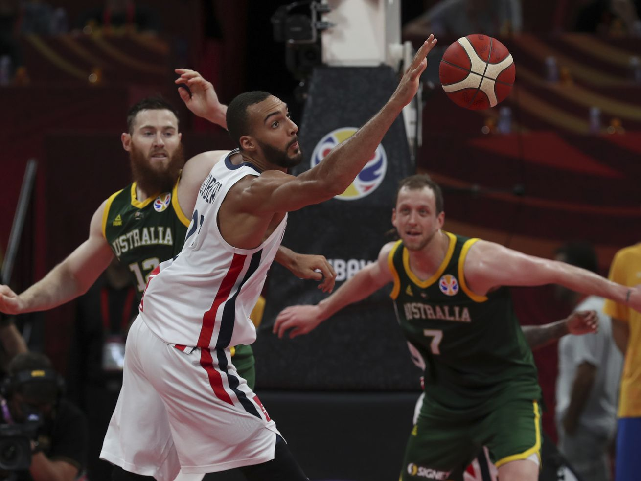 Rudy Gobert of France reaches for the ball over Aron Baynes, left, and Joe Ingles of Australia at FIBA Basketball World Cup.