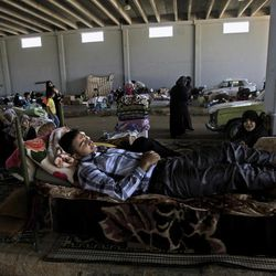 In this Wednesday, Sept. 12, 2012, photo, a Syrian man who fled his home in Marea 23 days ago, due to fighting between the Syrian army and the rebels, sleeps on a bed, as he and his family take refuge at Bab Al-Salameh crossing border, hoping to cross to one of the refugee camps in Turkey, near the Syrian town of Azaz. The days are still hot across the fertile plains of northern Syria, but at night there is a hint of a chill an ominous harbinger of winter's approach and the deepening of the humanitarian crisis gripping a country wracked by civil war.