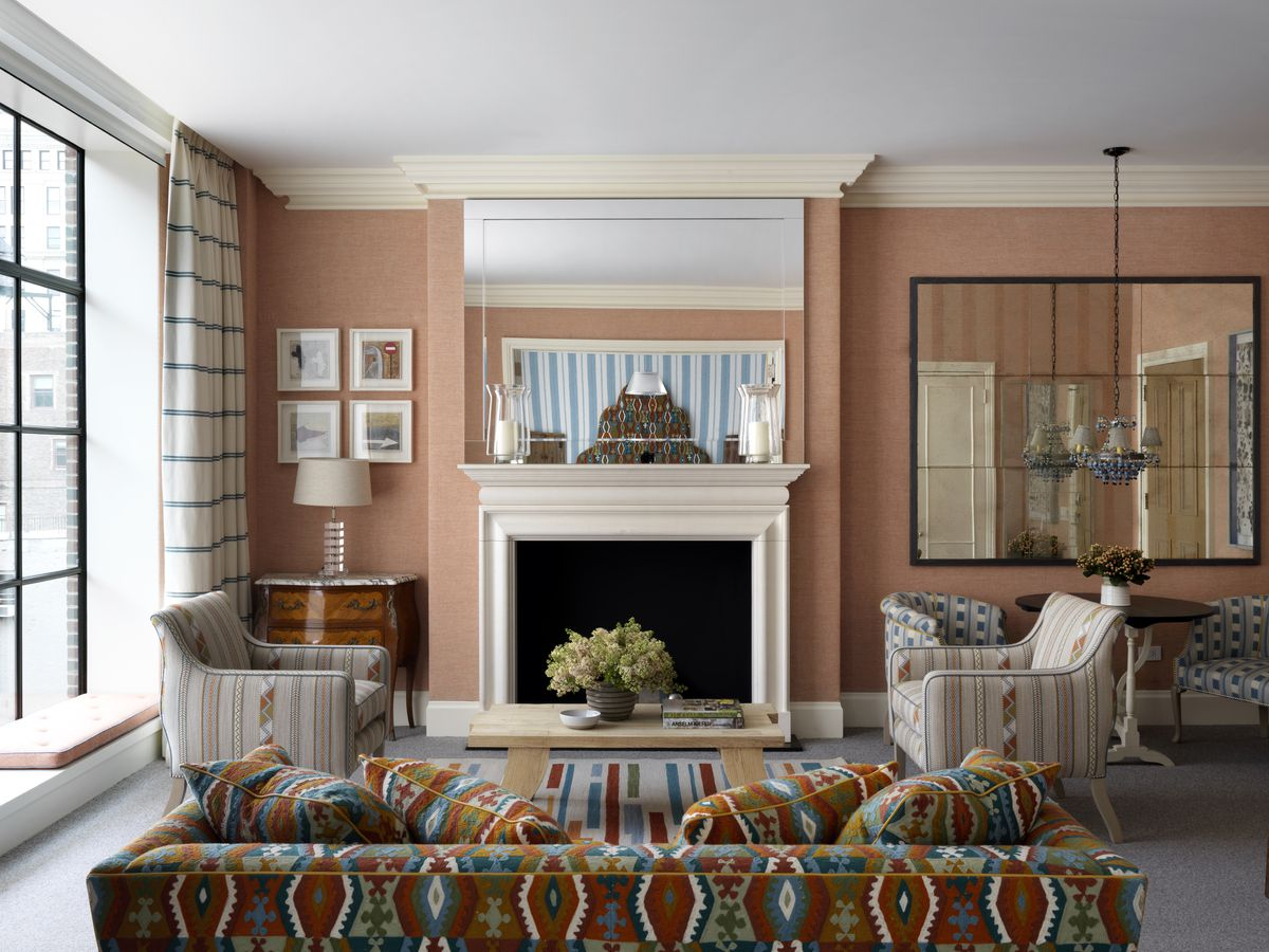 A guest room suite with terracotta walls and a fireplace.
