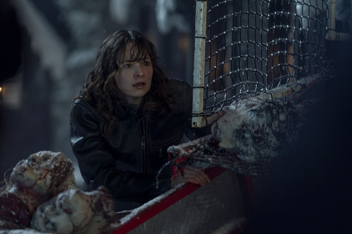 Ashleigh Cummings, with a bloody, swollen eye, looks nervously around a crumpled fence and a pile of indistinct severed heads in season 2 of NOS4A2.