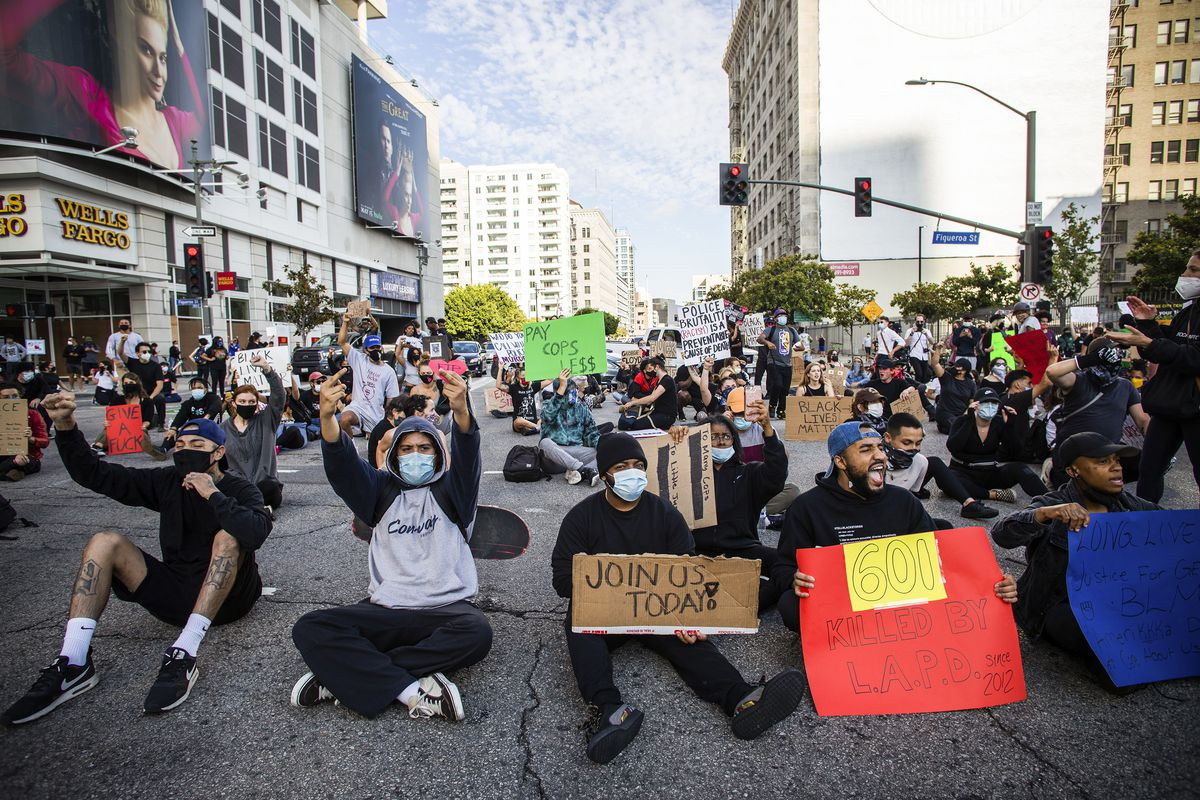 "A man bearing a red and yellow sign reading, ""601 killed by the LAPD,"" sits in the middle of the street. Around him, people raise their fists."