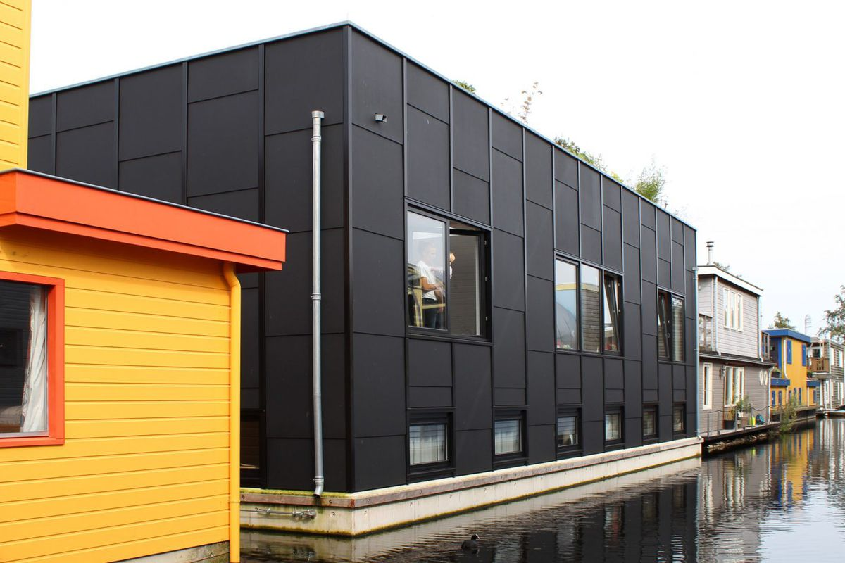 Modern black-timber box floats on water beside a row of other houseboats.