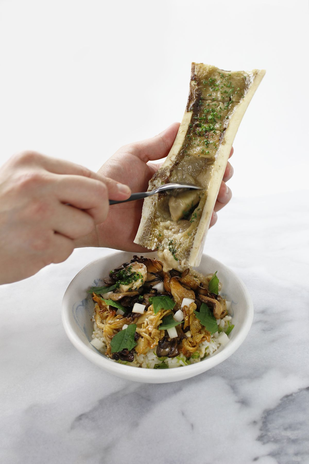 Two hands holding a white piece of bone scrape marrow with a spoon into a white bowl filled with rice and vegetables