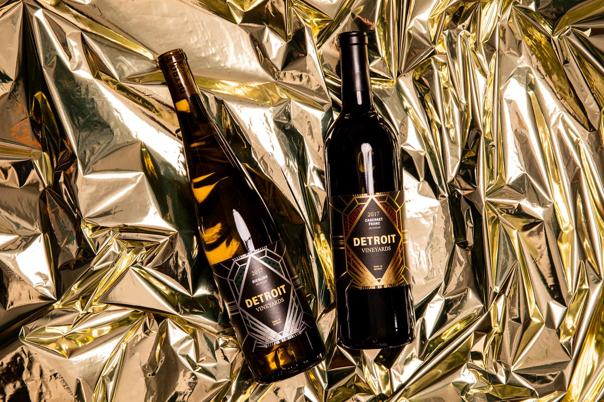 Two bottles of wine from Detroit Vineyards on a gold cellophane background.