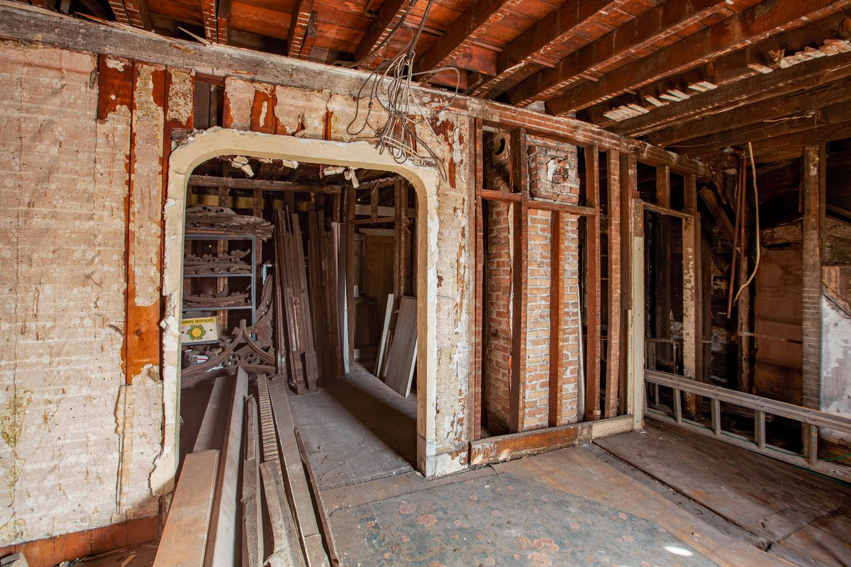 A room with exposed brick walls and wood beams on the ceiling. There's long pieces of wood stacked on the floor.