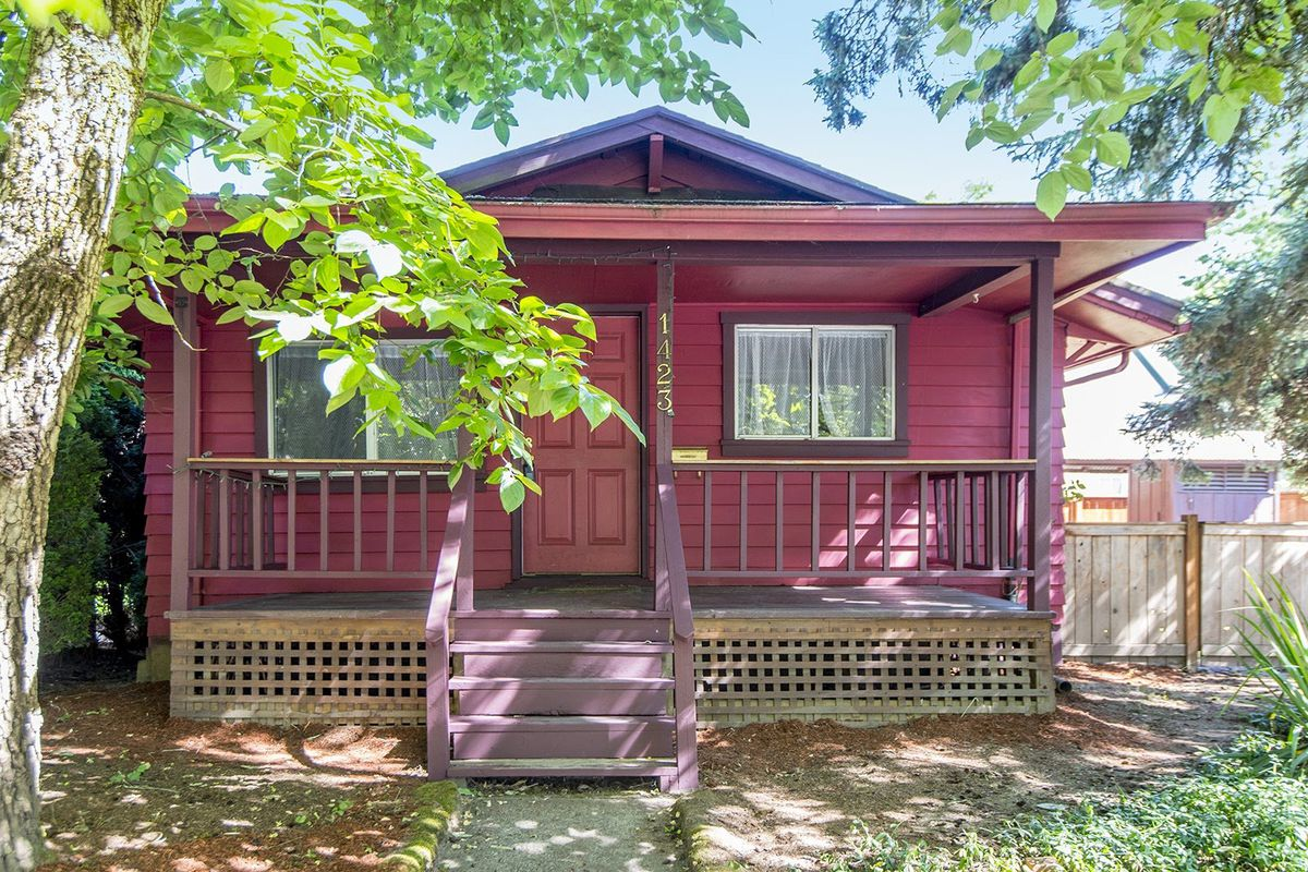 Exterior shot of dark red-painted bungalow with front porch.