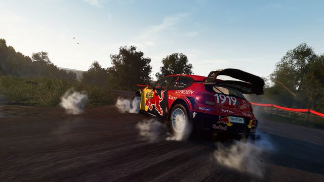 closeup of a rally car doing a tires-smoking burnout on pavement in WRC 8