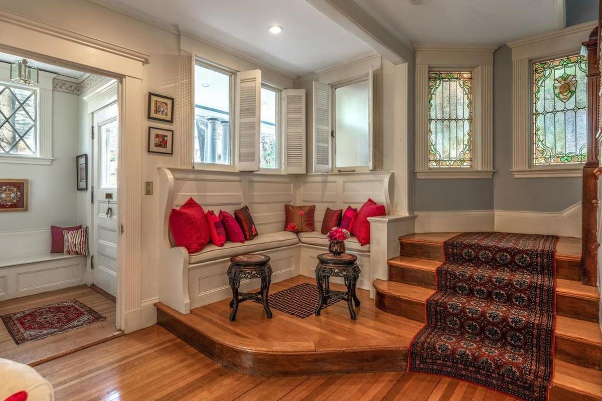 An entry foyer with a pillow-covered built-in bench next to a staircase.