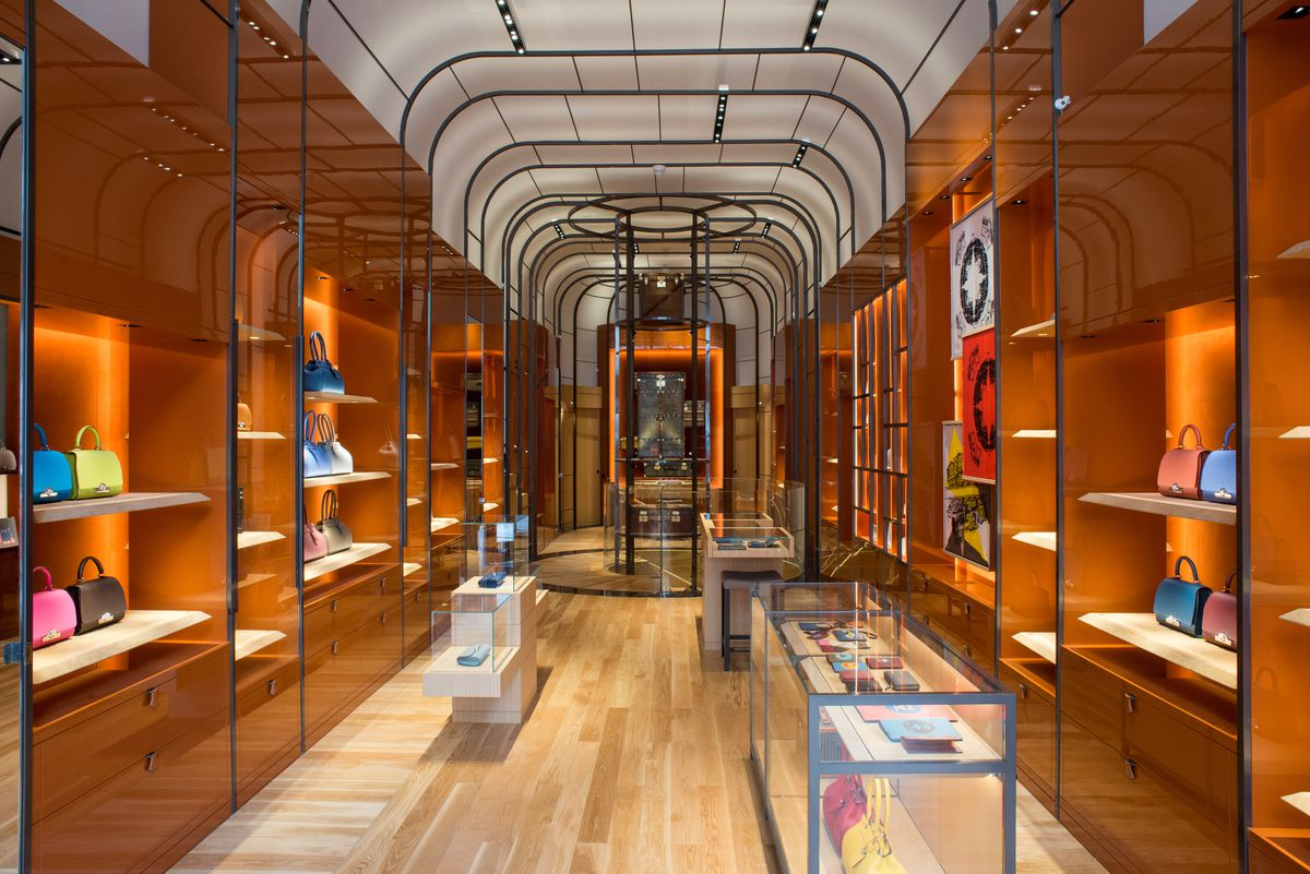 A hallway with wooden shelves and flooring inside Moynat's New York City store.