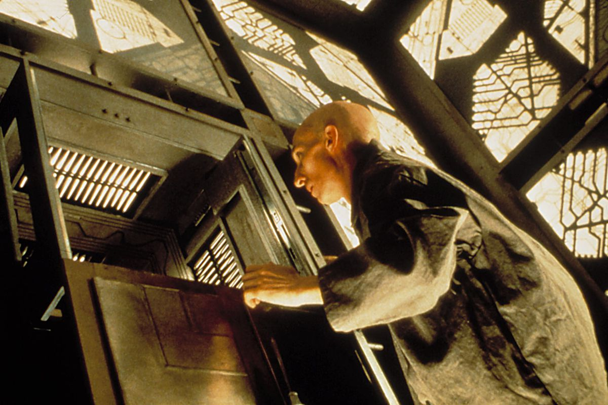 A bald man approaches an aperture in a grid-based wall in the science fiction movie Cube