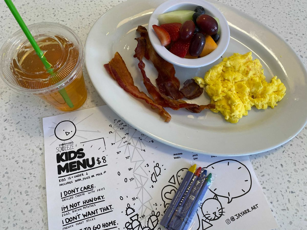 A plate of bacon, eggs, fruit, and a plastic to-go cup filled with tea next to a kids menu and crayons on a white speckled formica table.