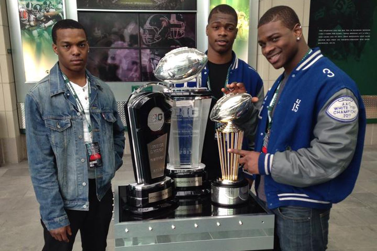 Larry Scott might be posed with the Michigan State trophy, but he's thinking hard about the Buckeyes.