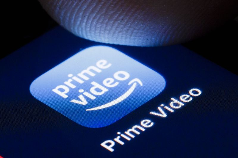 The Amazon Prime Video logo on a phone screen with a thumb hovering over it.