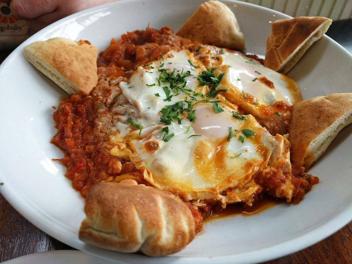 Shakshuka at Meme Mediterranean with five pieces of bread surrounding the white bowl, filled with a red tomato-based sauce.