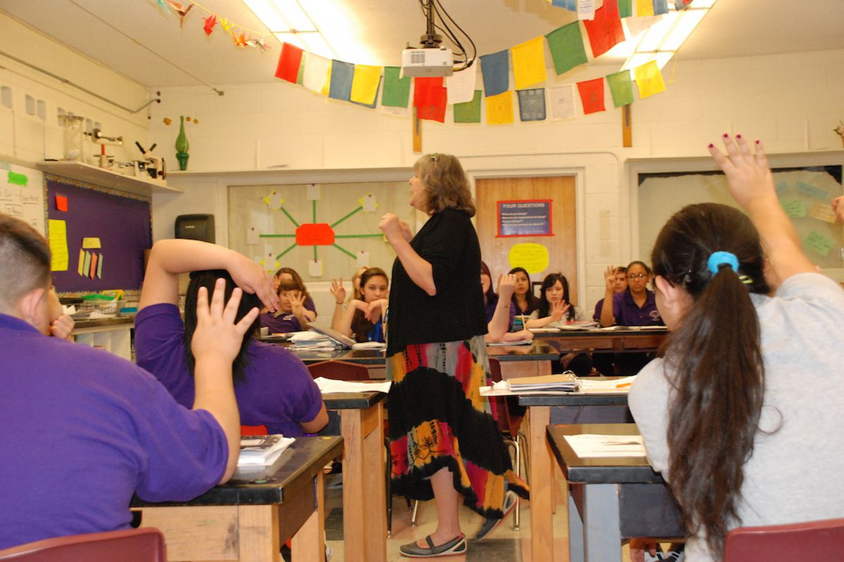 Students at the Pueblo Academy of the Arts raise their hands to answer a science question.