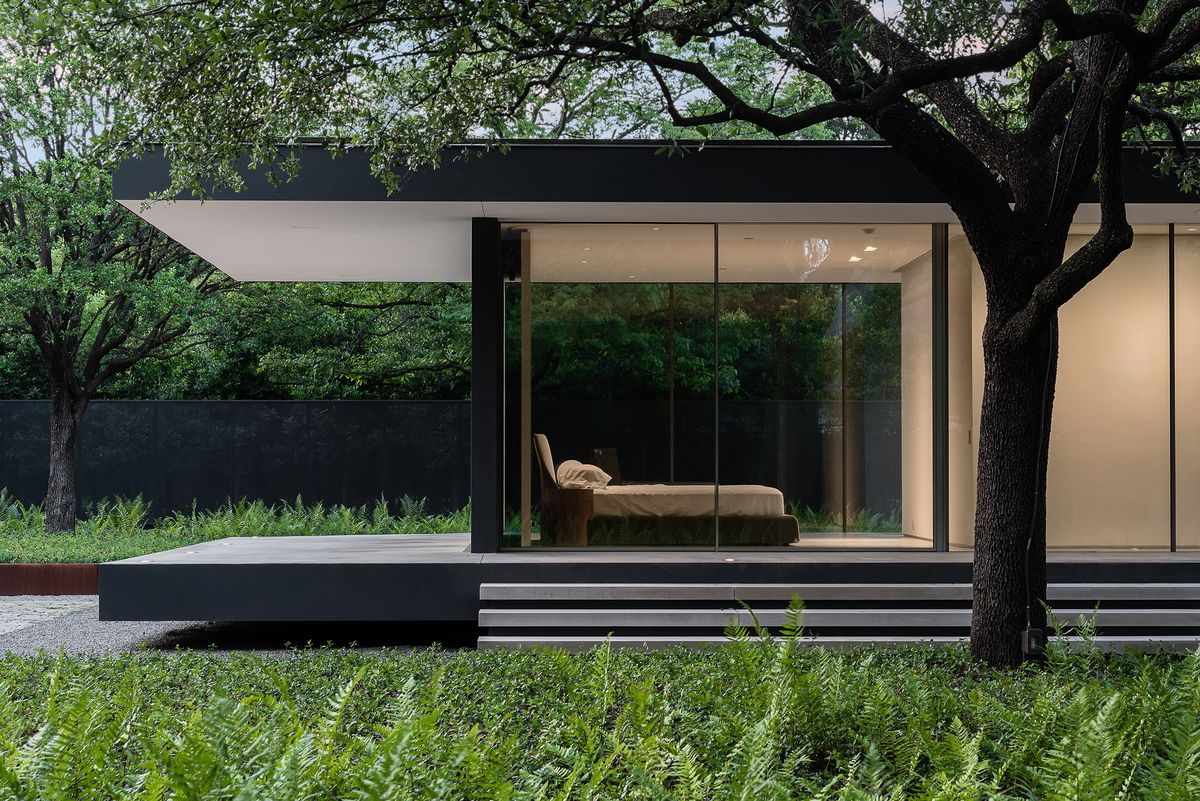 An exterior view of a house with overhanging room and glass walls that look into the bedroom.
