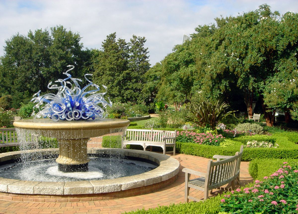 An outdoor area at the Atlanta Botanical Garden. In the foreground is a fountain with a blue glass sculpture on the top. In the distance are various trees, plants, and flowers.