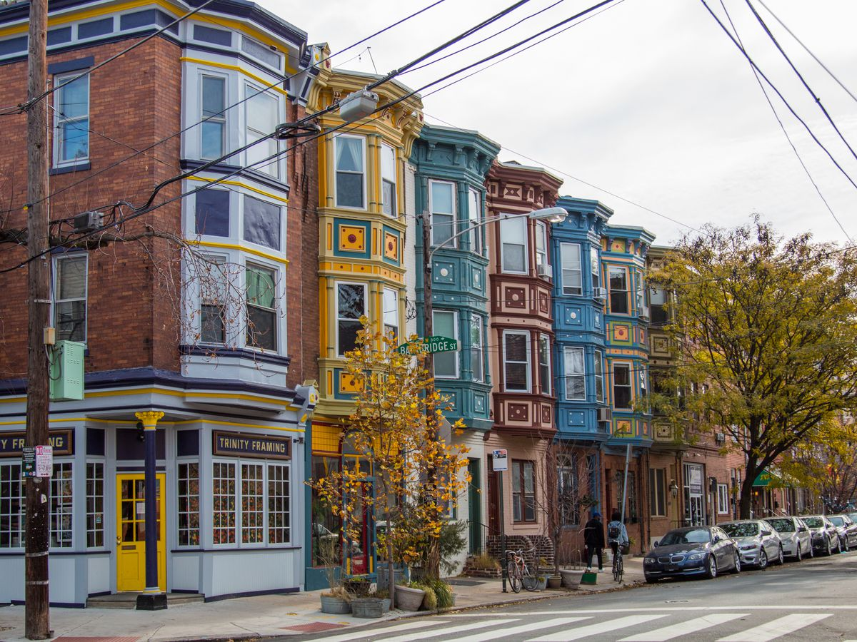 A row of colorful houses in Philadelphia known as Fabric Row. There are various fabric stores and shops on the ground floors of the buildings.