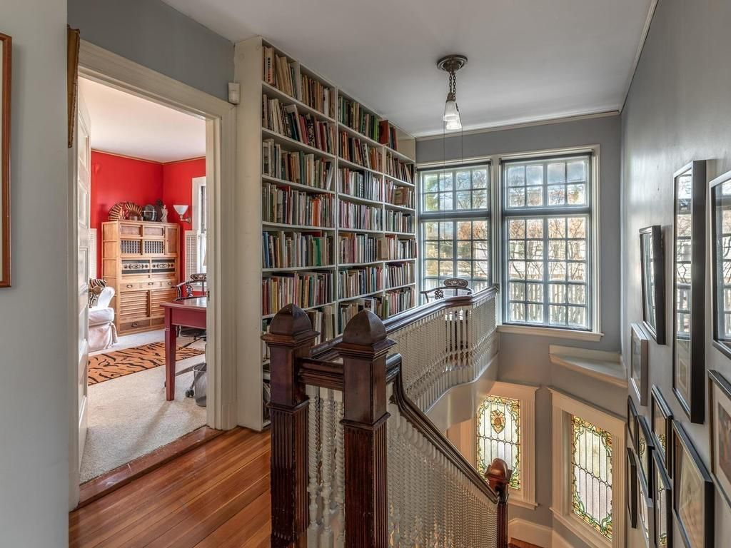 The top of a staircase with floor-to-ceiling bookshelves in the hall and big windows.