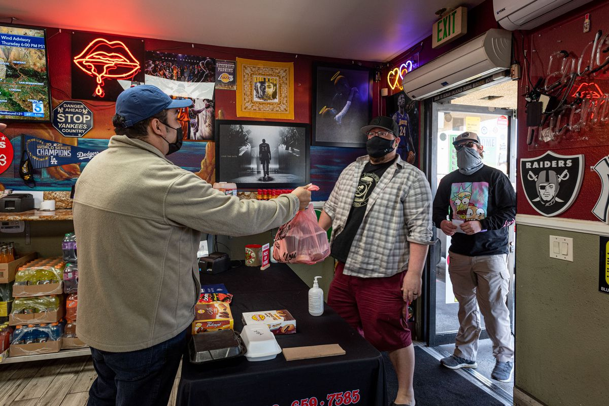 Two customers in masks pick up food inside of a neon-lit restaurant in Los Angeles area.