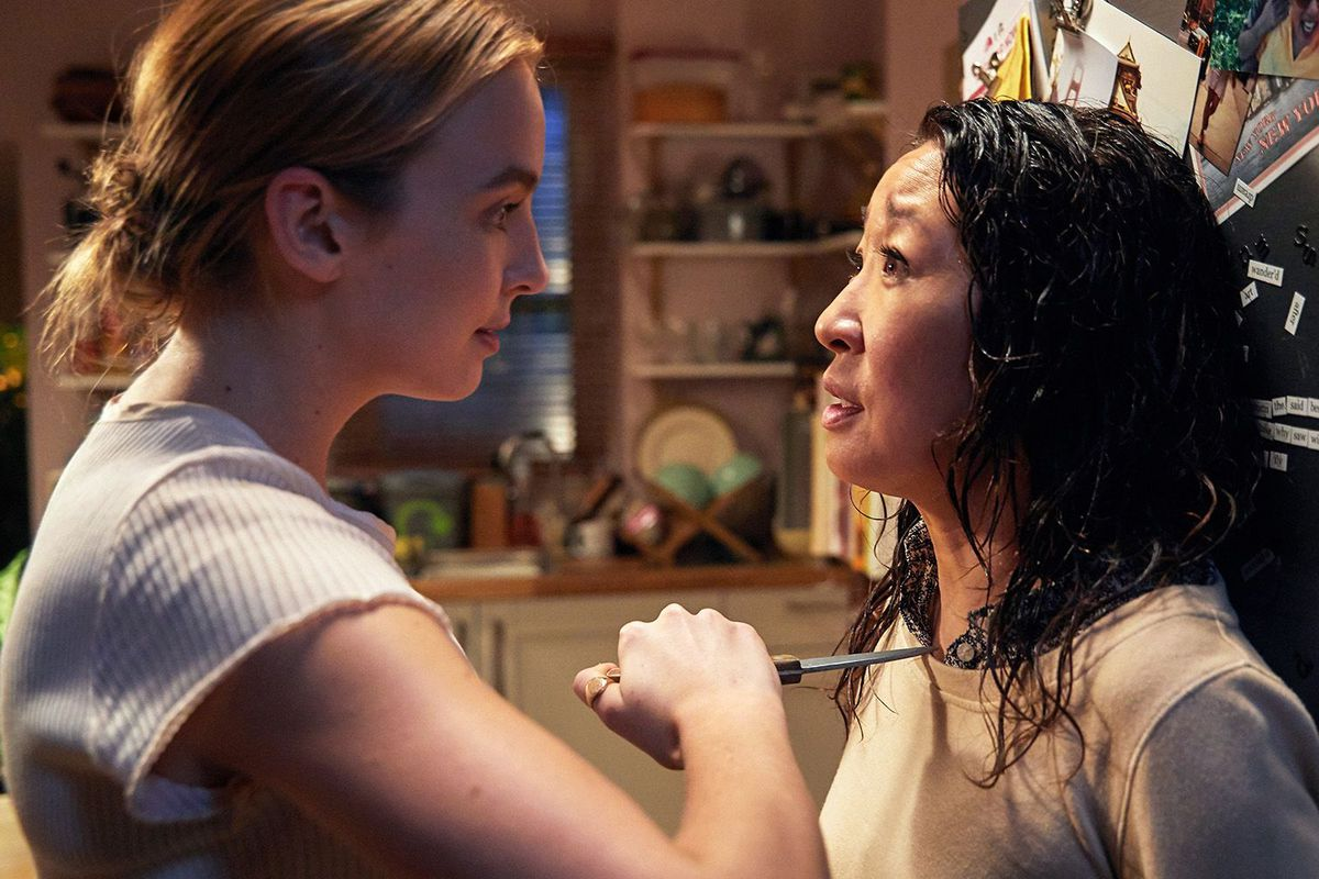 Killing Eve Season 3's Sandra Oh and Jodie Comer stand by a fridge, with Comer holding a knife to Oh's chest