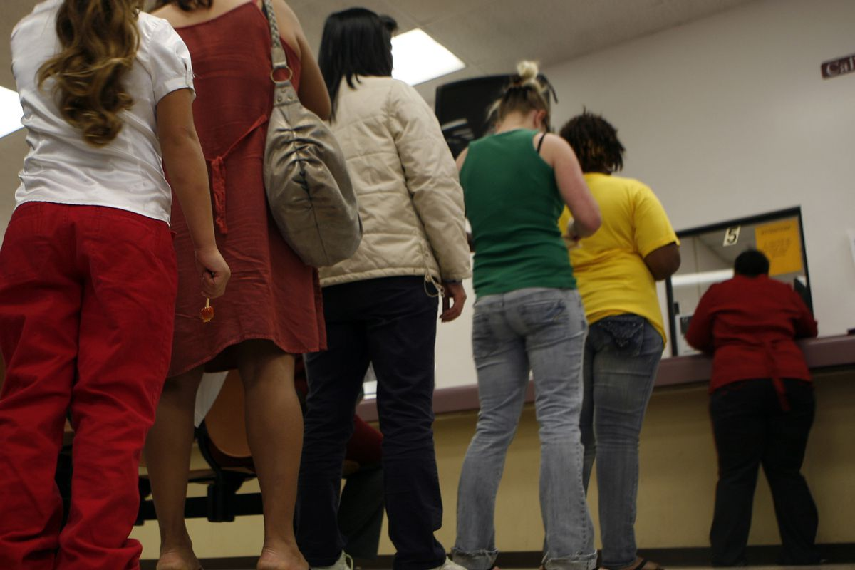 Laid-off workers stand in line for unemployment benefits at the Los Angeles Department of Public Social Services office.